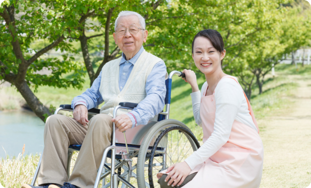 elder man in a wheelchair with a caregiver